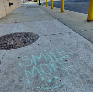 Smile more words on the sidewalk written in chalk