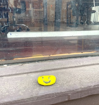 Painted smile rock on window ledge