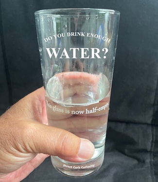 half empty glass of water promoting the podcast street curb curiosity