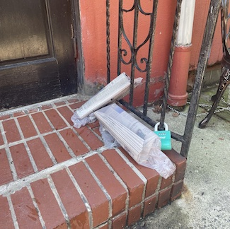 newspapers on a porch, untouched and unread