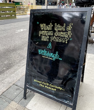 sidewalk sign outside a pizza shop used to promote a podcast