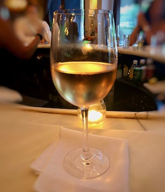glass of white wine at a bar