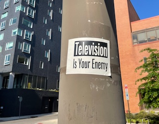 Television is the enemy poster on a pole in a city street