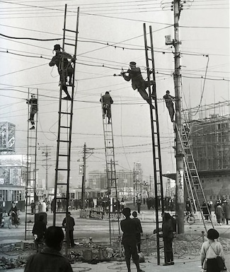 old photo of workers repairing overhead wires